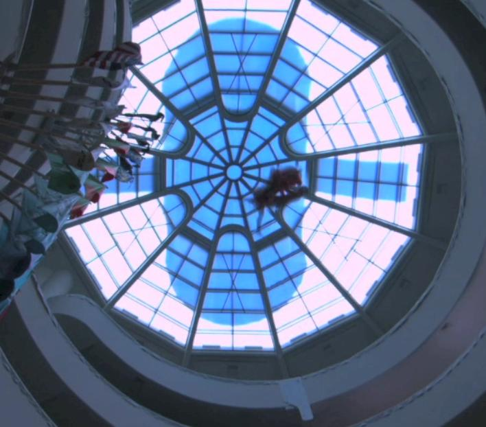 Illustration 2: The Apprentice and Aimee Mullins flying across the Guggenheim's ceiling. Screenshot from: Barney, Matthew. 'The Order.' <em>Cremaster</em><em> 3. © </em>Matthew Barney